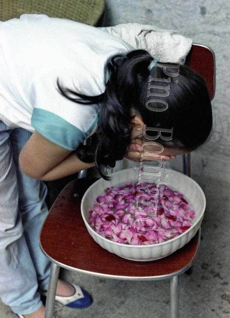 Lavacro del viso con l'acqua della notte di San Giovanni.Arcinazzo Romano (RM), 24-6-1985. Al mattino del 24 giugno ci si lava il viso con acqua e petali di rose, in recipienti lasciati sotto il cielo della notte, per raccogliere la rugiada, ritenuta piena di proprietà curative per la pelle.