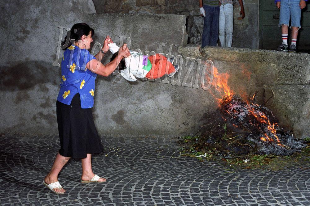 """Dondolamento di un bambino al """"fuoco santo"""". Arcinazzo Romano (RM), 23-6-1991. Nella notte di San Giovanni i bambini piccoli venivano dondolati in direzione del fuoco per scongiurare la malattia del rachitismo."""