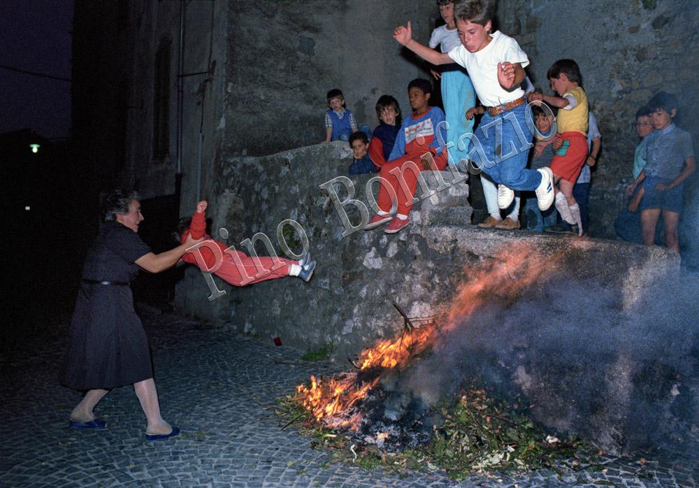 """Bambini che saltano sul """"foco santo"""". Arcinazzo Romano (RM),24 giugno 1986. Nella notte di San Giovanni i bambini saltavano sul fuoco o venivano dondolati per scongiurare il rachitismo e crescere più alti."""